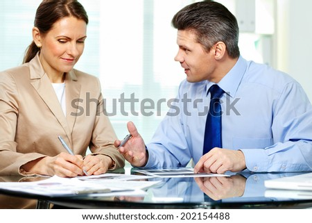 Business partner explaining new strategy to elegant business woman - stock photo