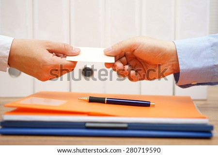 business partners are exchanging business cards over documents after meeting - stock photo