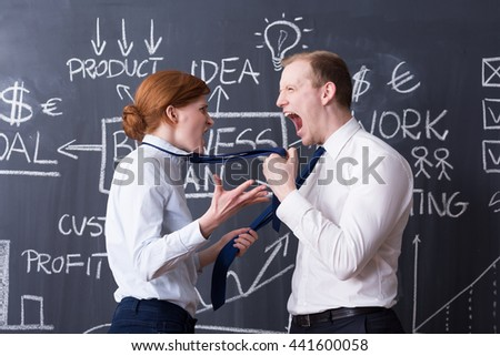 Business partners arguing, shouting at each other, business plan drawn on a blackboard in the background