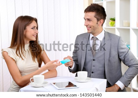 Business partners changing business cards in cafe