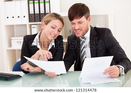 Business partners discuss sales basing through graphs. - stock photo