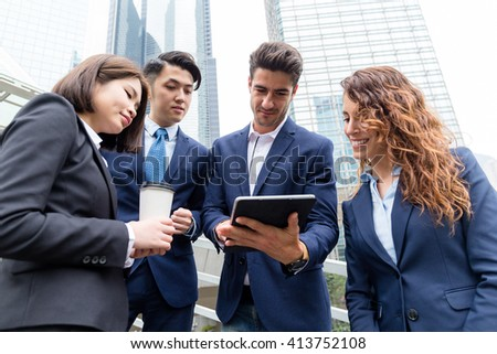Business partners discuss something on tablet computer - stock photo