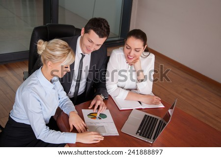 business partners discussing documents and ideas at meeting in office