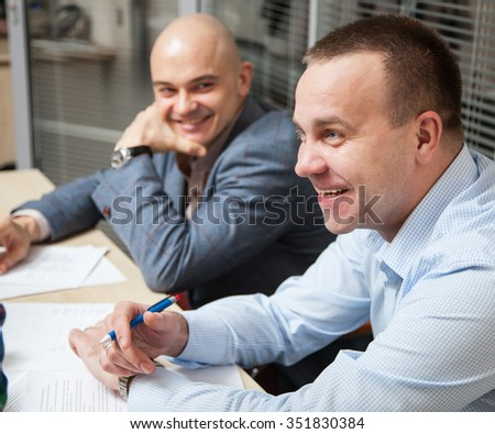 Business partners discussing ideas at meeting, neutral background