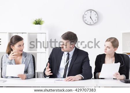 Business partners during meeting, talking, sitting beside desk in light office