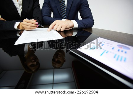 Business partners hands during reading contract - stock photo
