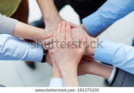 Business partners hands on top of each other symbolizing companionship - stock photo
