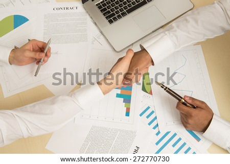 Business partners handshaking over business objects on workplace. - stock photo