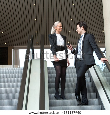 Business partners having conversation on escalator in mall. - stock photo