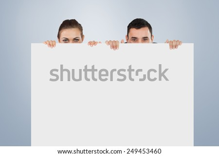 Business partners hiding behind a sign against grey vignette - stock photo