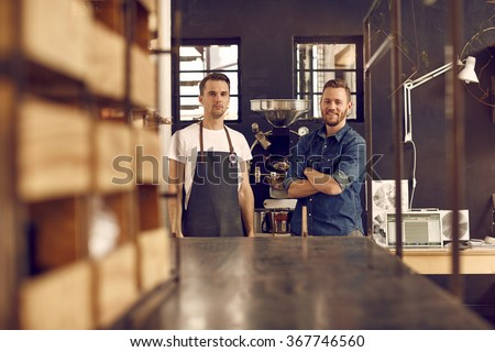 Business partners in a coffee roastery with new equipment - stock photo
