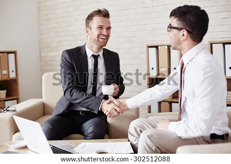 Business partners in formalwear greeting one another in office - stock photo