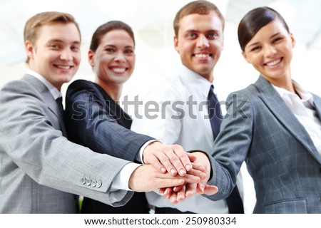 Business partners keeping their hands on top of each other - stock photo