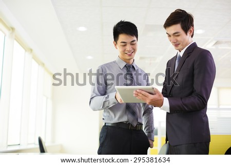 business partners looking at tablet and discussing - stock photo