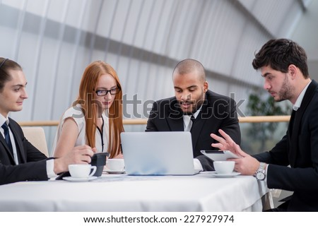 Business partners meeting with clients. Four smiling successful businessmen sitting at table in office while discussing their business doings. Young men dressed in formal wear - stock photo