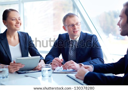 Business partners planning work and discussing ideas at meeting - stock photo