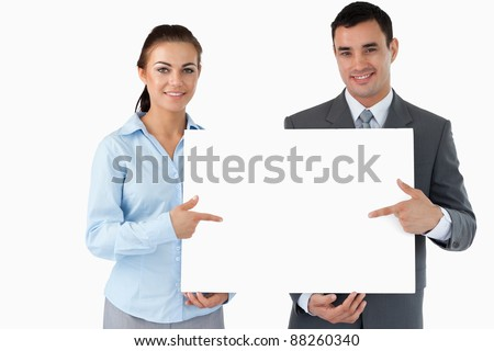 Business partners presenting sign together against a white background