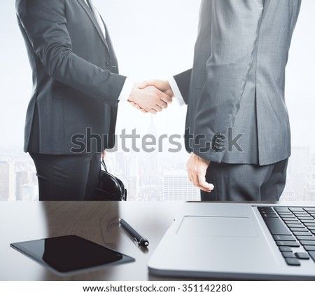 Business partners shake hands and table with laptop and diary - stock photo
