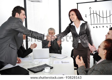 Business partners shaking hands after making deal while their co-workers applauding - stock photo