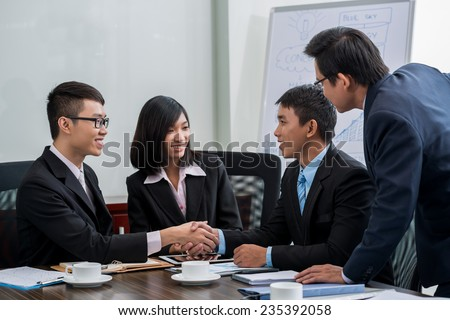 Business partners shaking hands after successful meeting