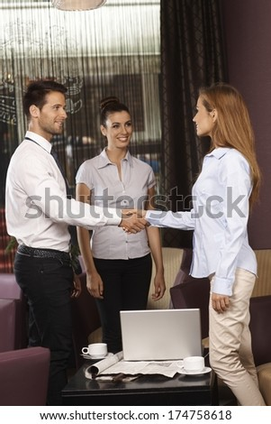 Business partners shaking hands at meeting in hotel lobby or bar. - stock photo