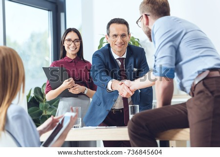 business partners shaking hands in modern office after conversation