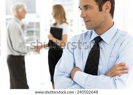 Business partners shaking hands in the background and executive man with arms crossed looking at them on foreground - focus on him - stock photo