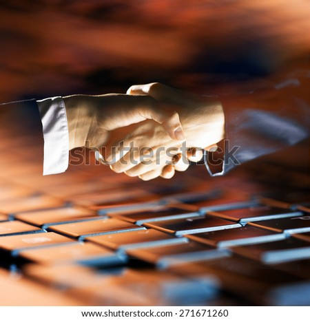 Business partners shaking hands over a laptop keyboard. Online business concept - stock photo