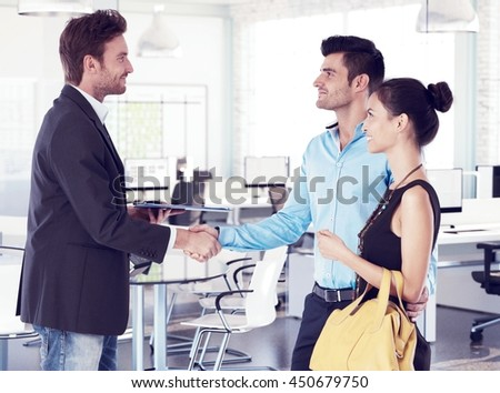 Business partners shaking hands, smiling. Side view.