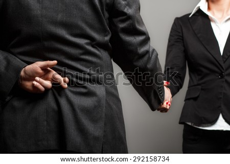 Business partners shaking hands with one of them holding fingers crossed behind back. - stock photo