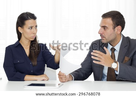 Business partners sitting at the table and angrily looking at each other.  - stock photo