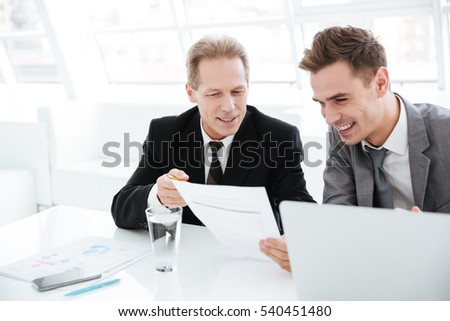 Business partners sitting by the table with documents and laptop