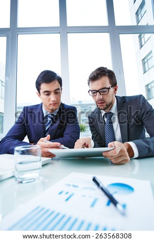 Business partners studying data in office - stock photo