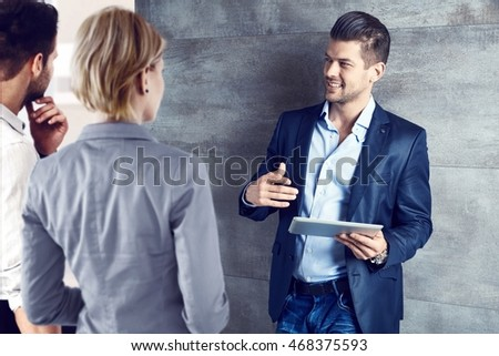 Business partners talking at office, young businessman using tablet.