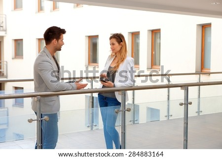 Business partners talking in corridor of apartment house. - stock photo