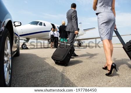 Business partners with luggage walking towards private jet at terminal - stock photo