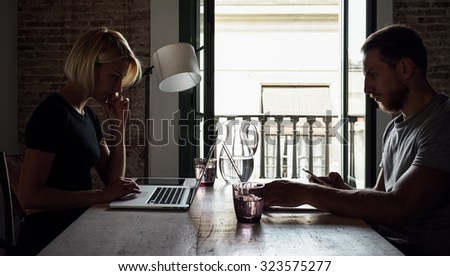 business partners working at desk  opposite each other. back light