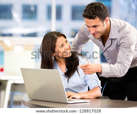 Business partners working at the office on a computer - stock photo