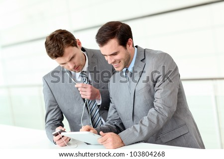 Business partners working in hallway with electronic tablet - stock photo