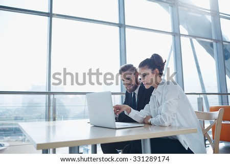 Business partners working on laptop at modern office - stock photo