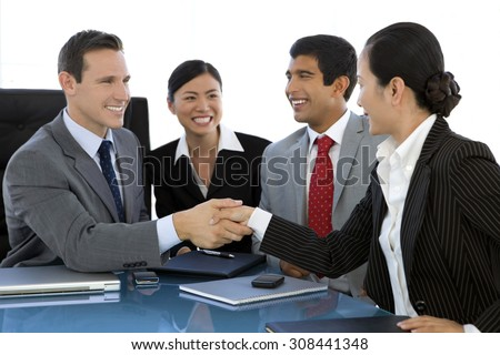 Business partnership. Caucasian businessman shaking hand of a Chinese businesswoman at a meeting. Two other business people witnessing. - stock photo