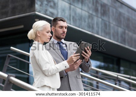 business, partnership, technology and people concept - businessman and businesswoman working with tablet pc computer on city street - stock photo