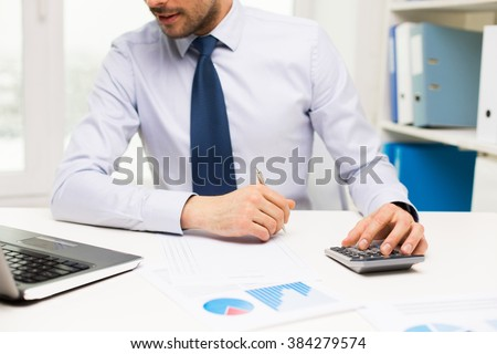 business, people, accounting and technology concept - close up of businessman with laptop computer, calculator and papers working in office - stock photo