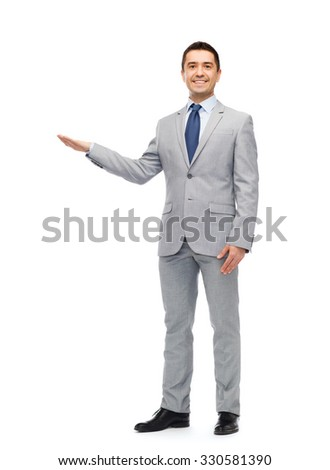 business, people, advertisement and office concept - happy smiling businessman in suit showing something imaginary - stock photo