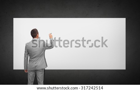business, people, advertisement , information and office concept - businessman writing or drawing something imaginary on white board from back over dark gray background - stock photo