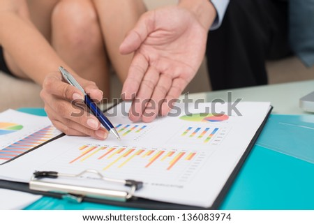 Business people analyzing financial statistics as a part of the annual report - stock photo
