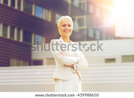 business, people and education concept - friendly young smiling businesswoman with crossed arms over office building - stock photo