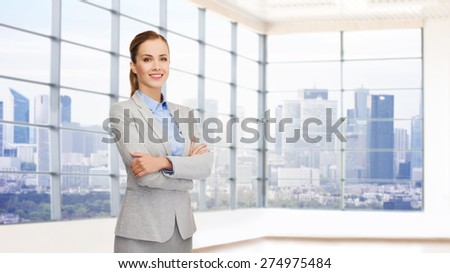 business, people and education concept - smiling young businesswoman with crossed arms over office room background - stock photo
