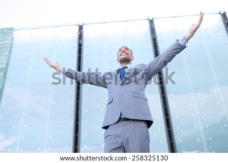 business, people and education concept - young smiling businessman with raised hands over office building - stock photo