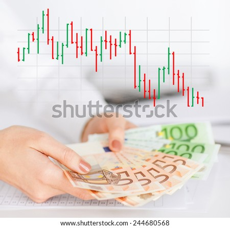 business, people and finances concept - close up of woman hands holding euro money over gray background with forex chart - stock photo